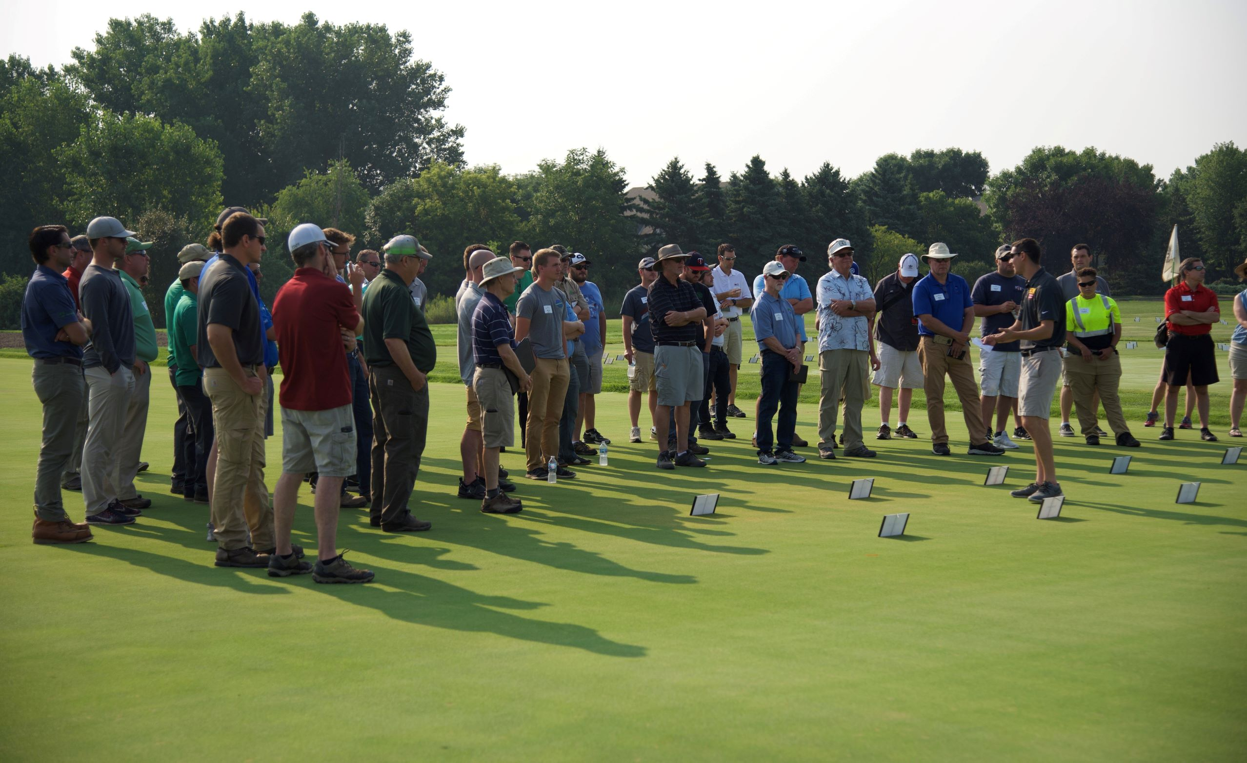 person on golf greens presenting research results to field day audience of 40 people
