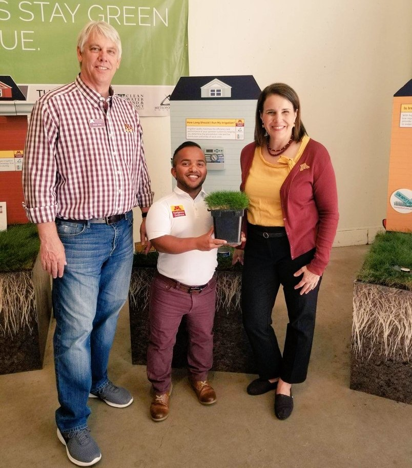 Three people stand in front of the turfgrass state fair display with a pot of fine fescue turfgrass