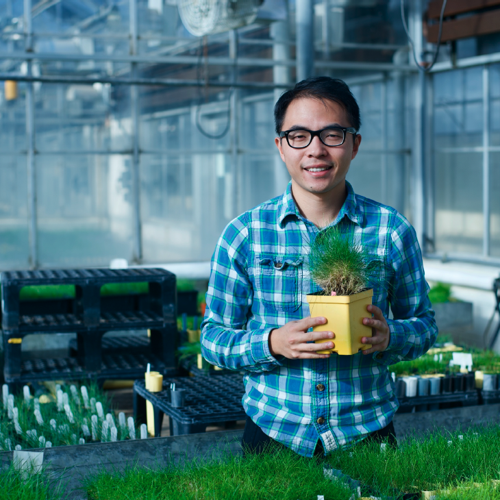 Yinjie Qiu in the greenhouse holding a planter with turfgrass